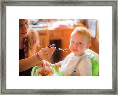 Mother Feeding Her Toddler In A High Chai Framed Print by Samuel Ashfield