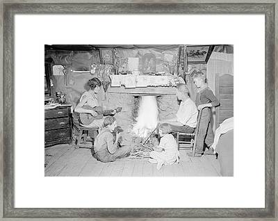 Mother Plays The Guitar While Family Framed Print by Stocktrek Images