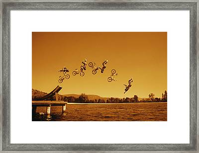Multiple Exposure Of Cyclist Going Off Framed Print