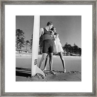 Nat Young And Marisa Berenson By A Surfboard Framed Print