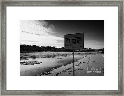 no swimming sign at the south saskatchewan river in winter flowing through downtown Saskatoon Saskat Framed Print by Joe Fox