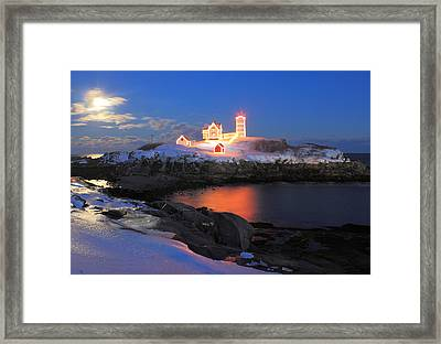 Nubble Lighthouse Holiday Lights And Winter Moon Framed Print by John Burk