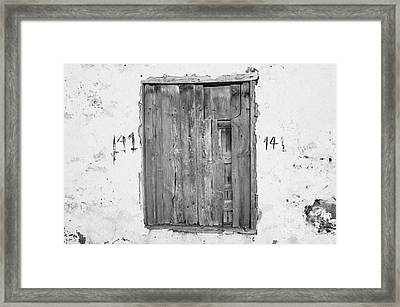 number 141 old weathered brown wooden window shutters on abandoned house with cracked stucco yellow walls in Tacoronte Tenerife Canary Islands Spain Framed Print