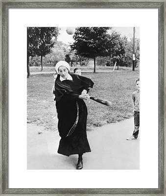 Nun Swinging A Baseball Bat Framed Print by Underwood Archives