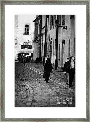 nun with briefcase walking up cobblestone street Kanonicza past tourists in old town krakow Framed Print by Joe Fox