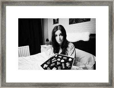 Offering Chocolates To Sceptical Early Twenties Woman In Bed In A Bedroom Framed Print by Joe Fox