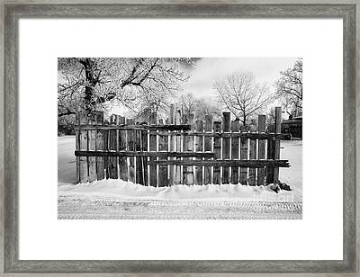 old patched up wooden fence using old bits of wood in snow Forget Saskatchewan  Framed Print by Joe Fox
