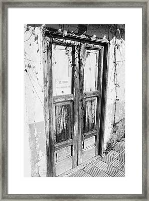 old weathered brown wooden door entrance to abandoned house with cracked stucco walls and for sale sign in spanish in Tacoronte Tenerife Canary Islands Spain Framed Print
