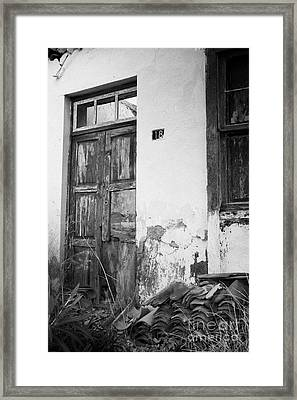 old weathered wooden door entrance to abandoned house 18 with window and cracked stucco walls in Los Banquitos Tenerife Canary Islands Spain vertical Framed Print