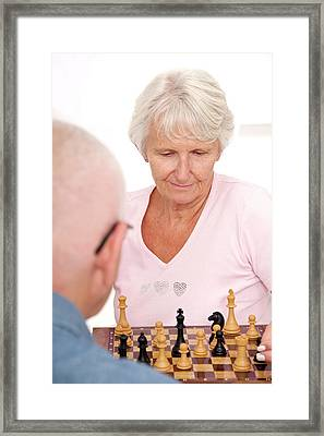 Older Couple Playing Chess Framed Print by Lea Paterson