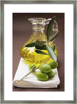 Olive Sprig With Green Olives, Carafe Of Olive Oil Behind Framed Print