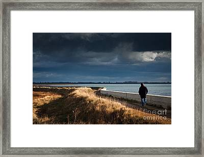 One Man Walking Alone By Sea Wall In Sunshine On Dramatic Stormy Framed Print