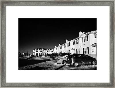 outdoor parking lot with vehicles outside row of condominium starter homes during winter Saskatoon S Framed Print by Joe Fox