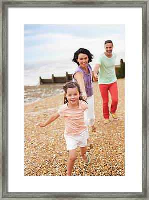 Parents Running On Beach With Daughter Framed Print