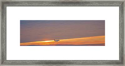 Passenger Airliner Landing At Dawn Framed Print by Jim West