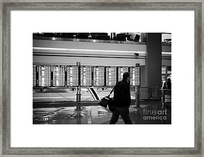 passenger walking past departures board at Denver International Airport Colorado USA Framed Print by Joe Fox