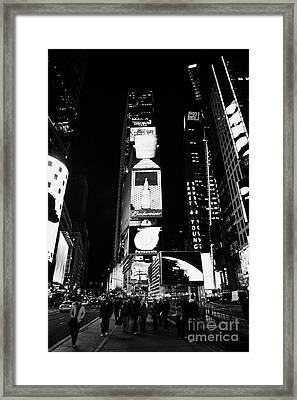 Pedestrians Walk In The Centre Of Times Square In Nighttime New York City Framed Print by Joe Fox