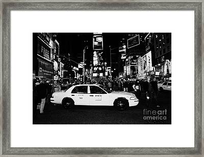 Pedestrians Walk Past Yellow Cab Stationary In The Middle Of Times Square At Night New York City Framed Print