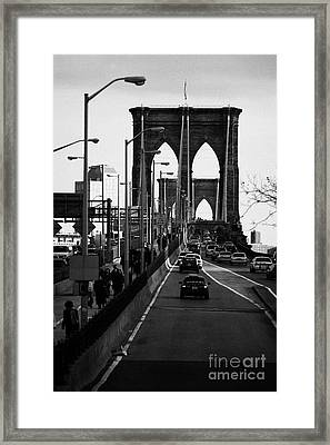 people and traffic crossing the Brooklyn bridge in the evening new york city Framed Print