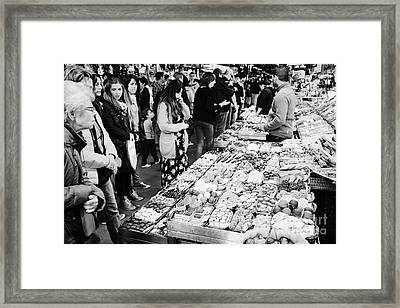 people buying chocolates on display inside the la boqueria market in Barcelona Catalonia Spain Framed Print by Joe Fox