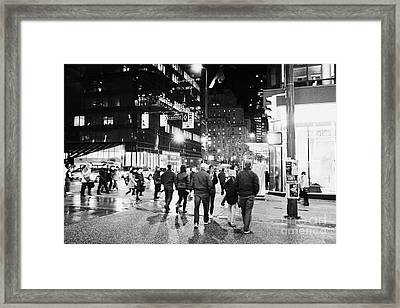 people crossing corner of granville and west georgia streets on a rainy night Vancouver BC Canada Framed Print by Joe Fox
