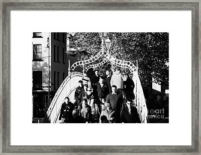People Crossing The Hapenny Ha Penny Bridge Over The River Liffey In Dublin At A Busy Time Framed Print by Joe Fox