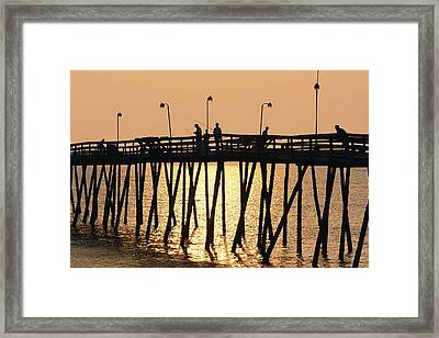 People On A Pier Are Silhouetted Framed Print by Steve Winter