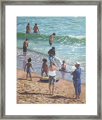 people on Bournemouth beach pulling dingys Framed Print by Martin Davey