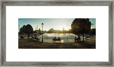 People Sitting At A Fountain With Blue Framed Print