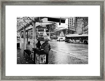 people standing in the rain waiting for a bus on burrard street downtown Vancouver BC Canada Framed Print