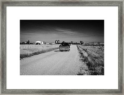pickup truck driving down rough unpaved rural road in farming community Saskatchewan Canada Framed Print by Joe Fox