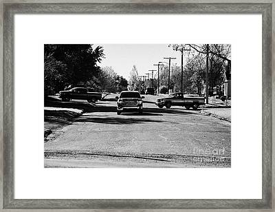 pickup trucks driving through street in small town in rural Saskatchewan Canada Framed Print by Joe Fox