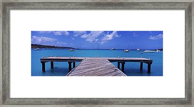 Pier With Boats In The Background Framed Print