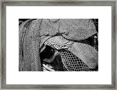 pile of small mesh fishing nets in the port harbour of Cambrils Catalonia Spain Framed Print