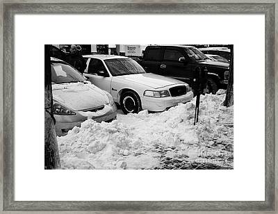 piles of snow cleared from sidewalk piled up at edge of sidewalk in front of parked cars Saskatoon Framed Print by Joe Fox