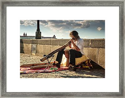 Playing Didgeridoo On The Charles Bridge. Prague Framed Print by Jenny Rainbow