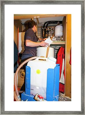 Plumber Fills A Solar Thermal Panel Framed Print by Ashley Cooper