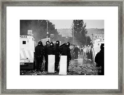 Police Officers In Riot Gear Face Rioters On Crumlin Road At Ardoyne Framed Print by Joe Fox