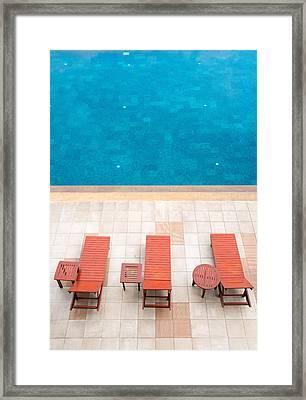 Poolside Deckchairs Alongside Blue Swimming Pool Framed Print by Jirawat Cheepsumol