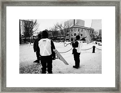 public workers clearing snow and ice off the sidewalks in downtown Saskatoon Saskatchewan Canada Framed Print