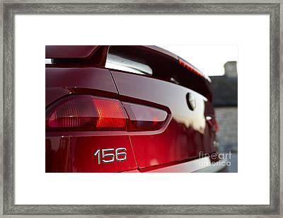 rear logo and brake lights on an Alfa Romeo 156 Framed Print by Joe Fox