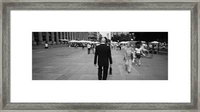 Rear View Of A Businessman Walking Framed Print by Panoramic Images