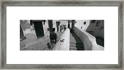 Rear View Of A Man Walking In Front Framed Print by Panoramic Images