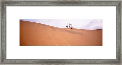 Rear View Of A Woman Carrying Panniers Framed Print by Panoramic Images