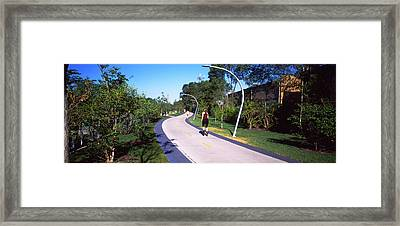 Rear View Of Woman Jogging In A Park Framed Print
