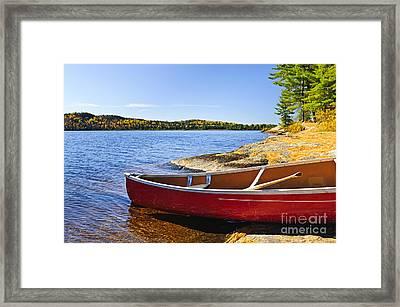 Red Canoe On Shore Framed Print