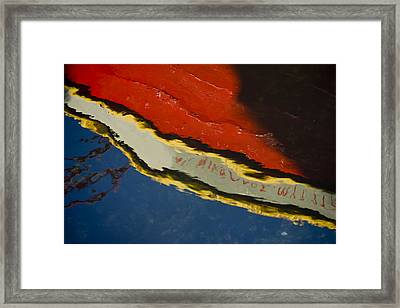 Reflection In Water Of Red Boat Framed Print by Raimond Klavins