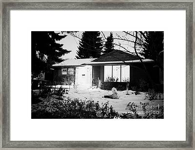 residential home at night in the snow with porch light on Saskatoon Saskatchewan Canada Framed Print by Joe Fox