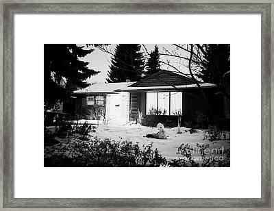 residential home at night in the snow with porch light on Saskatoon Saskatchewan Canada Framed Print by Joe Fox