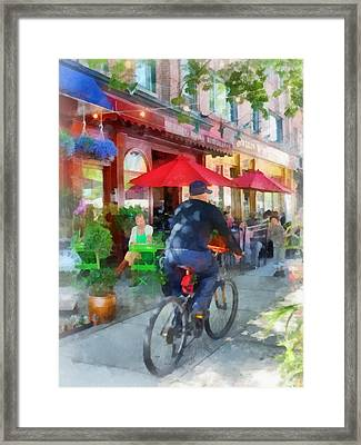 Riding Past The Cafe Framed Print by Susan Savad